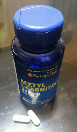 blue bottle of puritans pride acetyl l carnitine and capsules